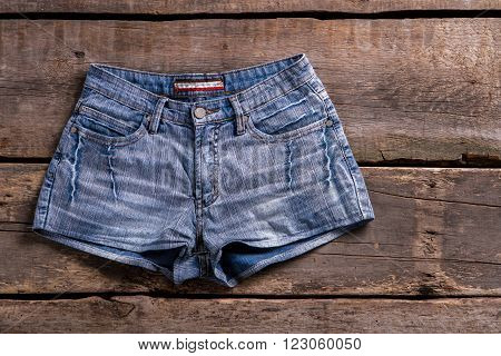 Denim shorts on vintage shelf. Shorts on old wooden table. Retro showcase with light shorts. New arrivals at retro boutique.