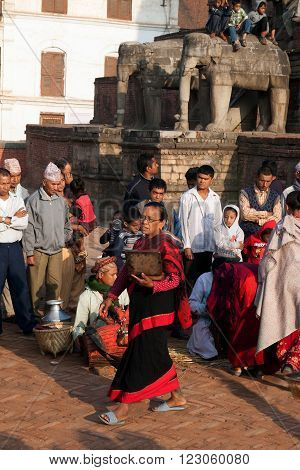 BHAKTAPUR NEPAL - APRIL 19 2013:Nepalese women - Newars make a religious ritual puja - offering sculptural image of the deity of food water incense flowers . Bisket Jatra is which is held during the celebration of Nepali New Year on the square in Bhaktapu