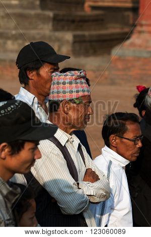 BHAKTAPUR NEPAL - APRIL 19 2013:Men of Bhaktapur in the national headdress -Dhaka Topi is participants and spectators watch a ritual dance called Bhairav Dance in Bisket Jatra is which is held during the celebration of Nepali New Year on the square in Bha