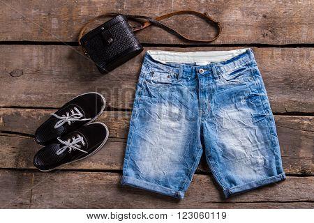 Lady's long blue denim shorts. Female clothing on aged shelf. Classic purse with denim shorts. Black keds and vintage handbag.