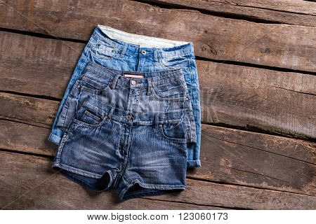 Pairs of different denim shorts. Woman's denim shorts on table. Vintage clothes shop's new arrivals. Classic shorts of different color.