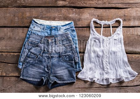Denim shorts with lace top. Lady's casual clothes on shelf. Stylish clothing at retro boutique. Summer sale of woman's clothes.