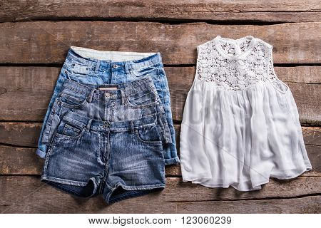 Different denim shorts and top. Woman's clothes on old floor. Light clothing at vintage store. Retro shelf with lady's garments.