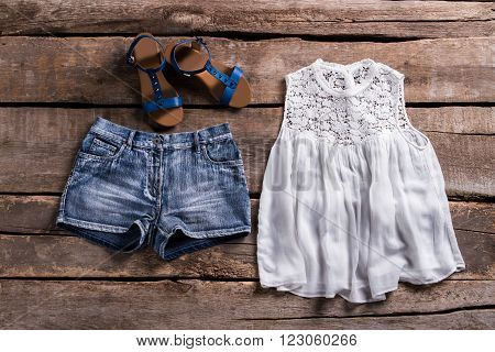 Top with shorts and sandals. Lady's outfit on aged table. Old shelf with female outfit. Showcase at retro clothing store.