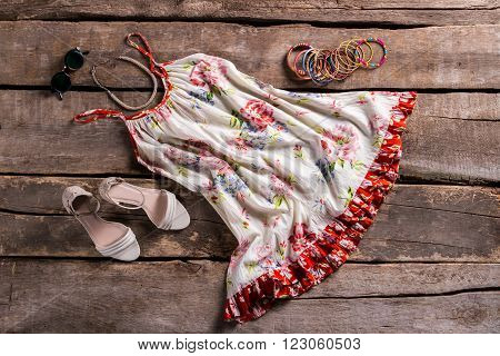Sarafan with footwear and accessories. Female outfit on brown shelf. Old table with lady's clothing. Vintage sarafan with colorful bracelets.