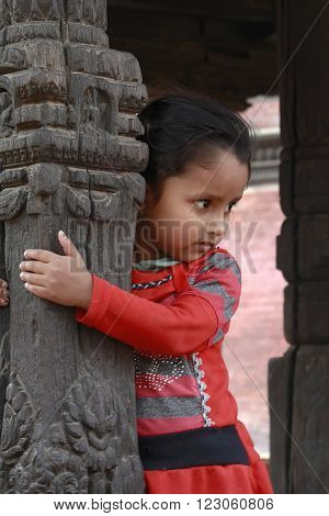 Lalitpur, Nepal -  April 16 2013: Little Girl Playing Near A Hindu Temple.