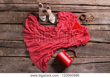 Dress and red cylinder purse. Clothing and purse on floor. Seasonal sale at vintage shop. Aged table with fresh garments.
