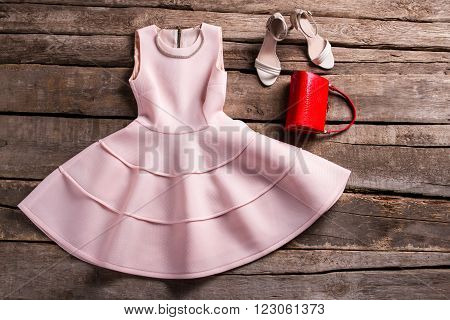 Red purse with salmon dress. Evening outfit on aged table. Fashionable outfit at vintage shop. Evening apparel for young ladies.