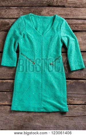 Turquoise dress with zipper pockets. Tuquoise dress on old shelf. Garment on aged wooden background. Woman's high-quality clothing.