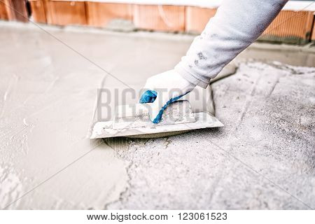construction worker using trowel and mason's float for hydroisolating and waterproofing house