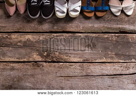 Female footwear on wooden floor. Shoes on wooden workshop shelf. Choose what you like. Summer footwear sale.