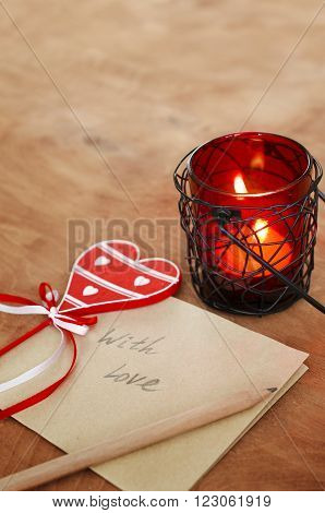 Card with Message With Love in the Letter, romantic candle holder with a candle and wooden red heart on a wooden table at Valentine Day