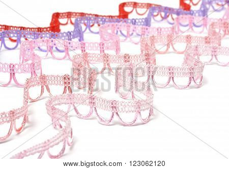 Curved strips of reddish lace on white background