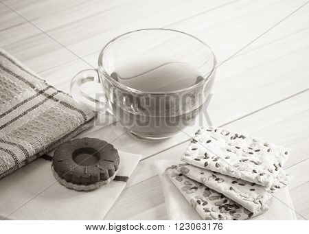 The composition of the tea beverage in a large bowl and some sweets on the table. Grain cookies, bagel. Foto in black and white.