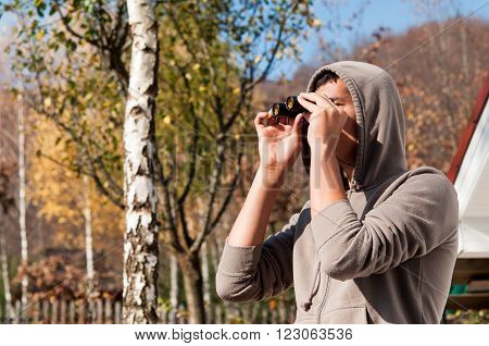 Young man with binoculars watching the nature Man with binoculars