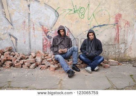Two Street Hooligans Or Rappers Sitting Against A Graffiti Painted Wall With A Ball Near Them