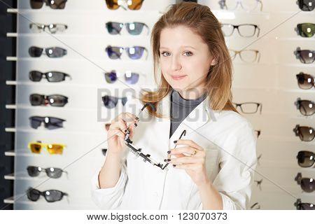 young beautiful blond optometrist showing new eyeglass