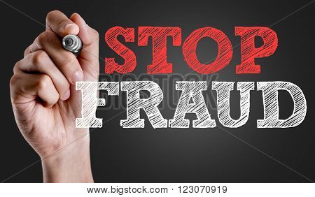 Hand writing the text: Stop Fraud