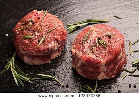 Raw Steak Meat on the dark surface. Dark background