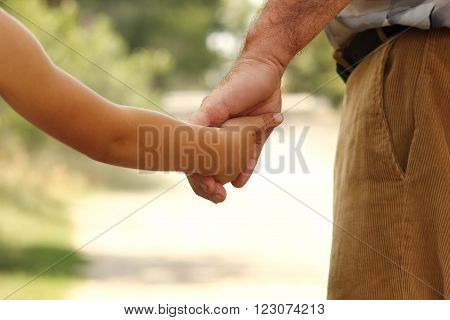 a the parent holds the hand of a small child