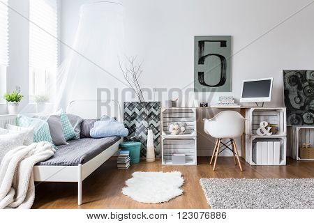 Cozy modern bedroom with hipster design. Single bed and wooden desk in room with wooden floor