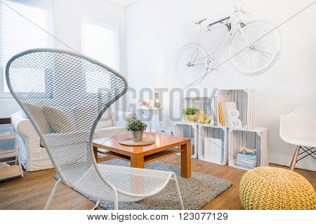 Cozy student's studio with modern stylish decor. Fancy armchair and wooden coffee table in living room