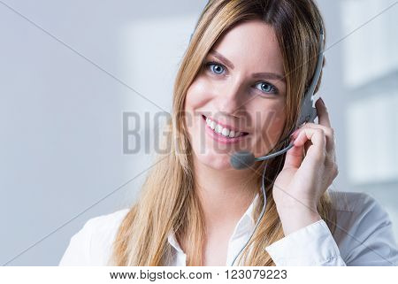 Female telemarketer with headphones taking care of client