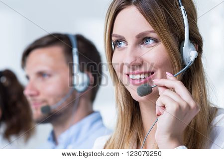 Young female telemarketer with headphones and work in corporation