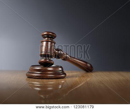 Mahogany wooden gavel on glossy wooden table.