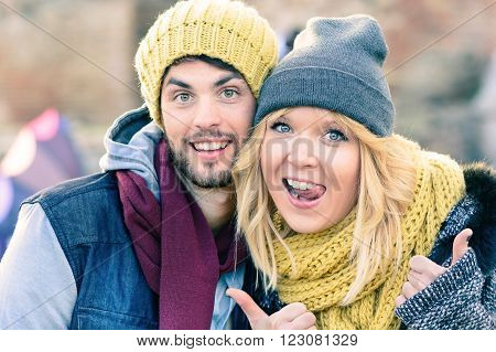 Happy hipster couple in love take a selfie photo during sunny day in autumn. Best friends with winter clothes sharing free time in the city and make shopping. Concept of lovers enjoying life moments.
