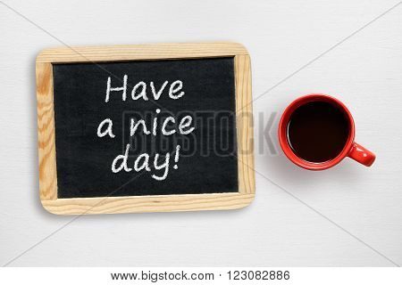 Have a nice day! wish and coffee cup on white table