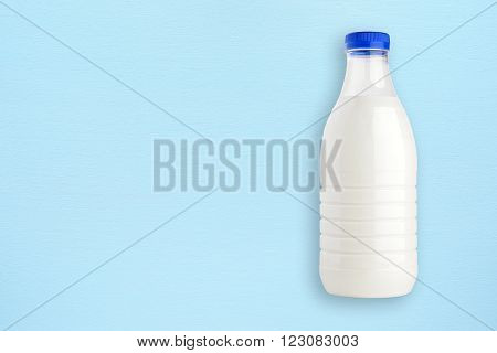 Milk bottle on blue wooden background with copy-space