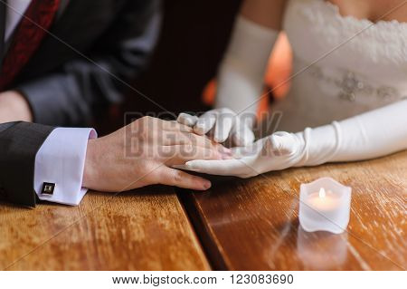 The groom holds the hand of the bride sitting at a wooden table. The candle on the table. the bride's hand in white gloves. The groom in a suit. Cuff shirt with cufflinks.