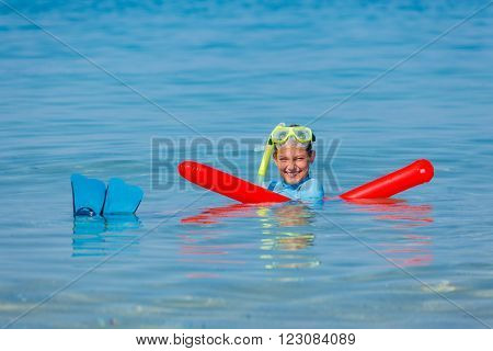 Joyful girl in mask and with flippers scuba diving.