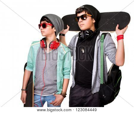 Portrait of two serious boys with skateboards posing in the studio, stylish teens isolated on white background, life of youth