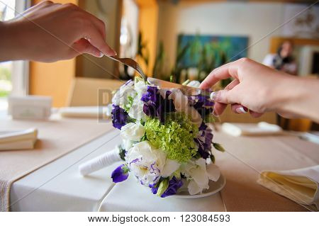 Joking photo, bride eating her bouquet at a restaurant with cutlery. bridal bouquet. Cutting brides' flower bouquet.