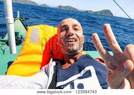 Man taking selfie on solo ocean crossing with tropical islands background - Tired male survivor to extreme travel experience - Concept of hard sea travel - Tilted horizon is part of the composition