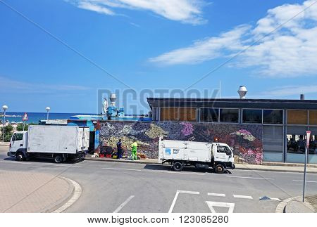 BARCELONA, SPAIN - JULY 31, 2015: Two workers talk in front of a storehouse between two trucks near Barcelona beach during a sunny summer day