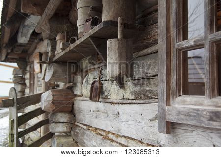 Ancient authentic ukrainian wooden hut wall with window and other retro self-made household