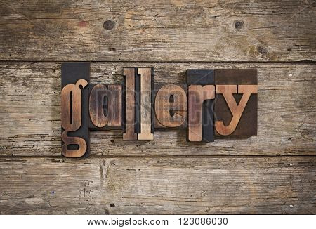gallery, single word set with vintage letterpress printing blocks on rustic wooden background