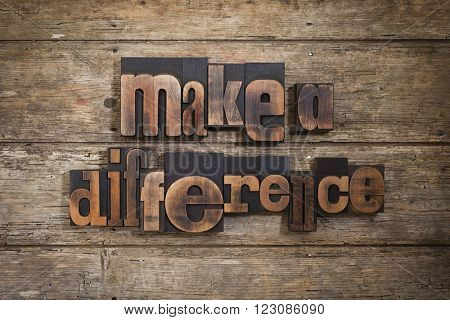 make a difference, phrase set with vintage letterpress printing blocks on rustic wooden background