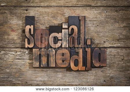 social media, phrase set with vintage letterpress printing blocks on rustic wooden background