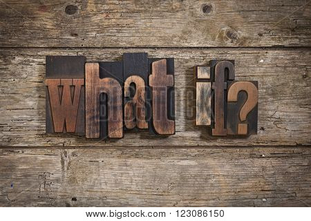 what if, phrase set with vintage letterpress printing blocks on rustic wooden background