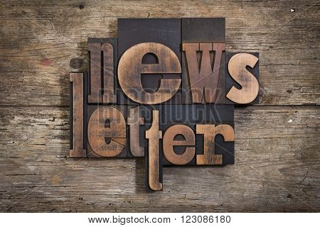 newsletter, word set in two lines with vintage letterpress printing blocks on rustic wooden background