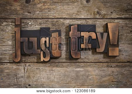just try, phrase set with vintage letterpress printing blocks on rustic wooden background