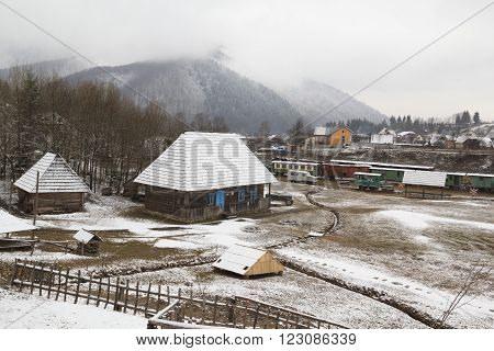 Old authentic ukrainian village in highland with railway station and misty mountain in background at winter.