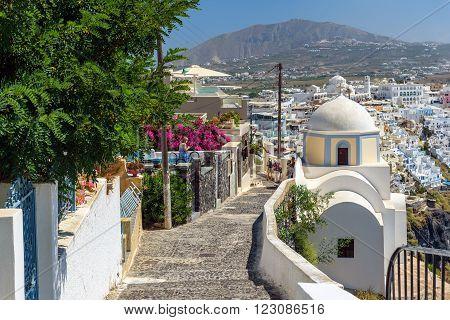 THIRA, SANTORINI, GREECE - AUGUST 24, 2015: Stony road to Thira town among churches and traditional houses on Santorini island, Greece