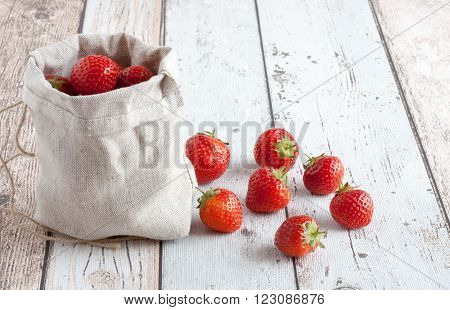 Fresh strawberries in a small hessian bag on a wooden style surface. Small group of strawberries on the table beside the bag.