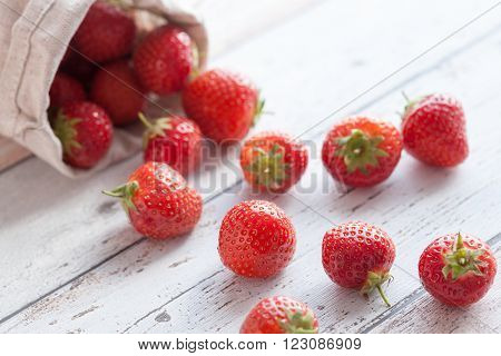 Fresh strawberries spilling out of a hessian bag on its side.