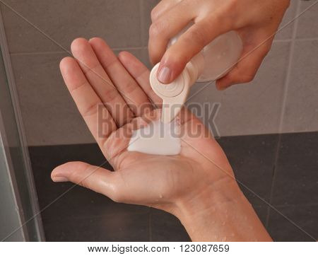 Pouring bath shower soap on hand
